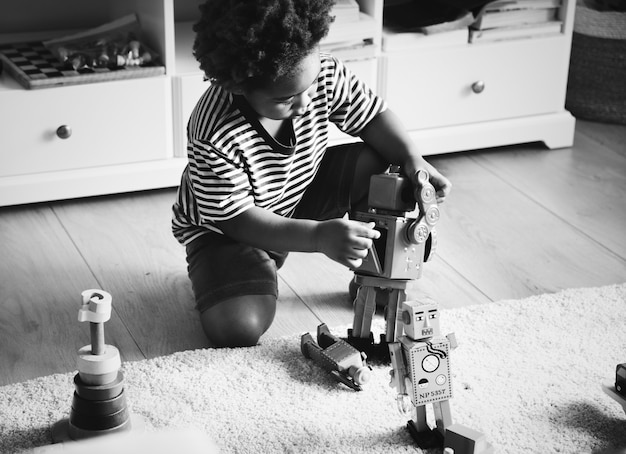 African boy playing with a robot at home Free Photo