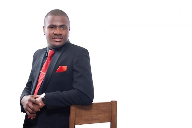 エレガントな黒のスイートと赤いネクタイを椅子に寄りかかって、一緒に手を繋いでいるアフリカのビジネス人。 無料写真