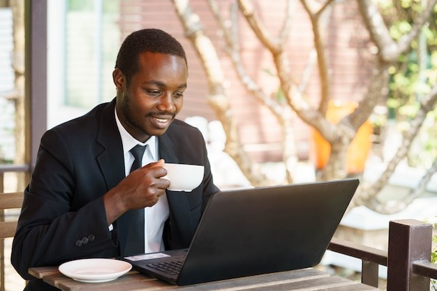 African businessman  holding coffee with smile and playing labtop. Premium Photo