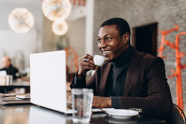 African businessman using phone and drinking coffee while working on laptop in a restaurant. Premium Photo
