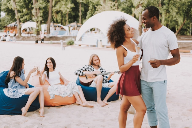 African couple have champagne dancing on beach Premium Photo