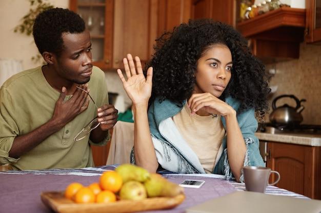 自宅でけんかを持っているアフリカのカップル。不幸な夫が言い訳を受け入れていない怒っている怒っている妻に不倫したことを謝罪する。許しを彼のガールフレンドに懇願する黒人男性 無料写真