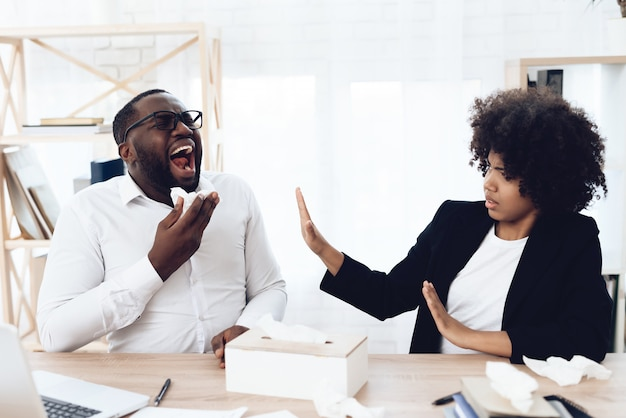 African coworkers sitting at table with man sneezing and coughing