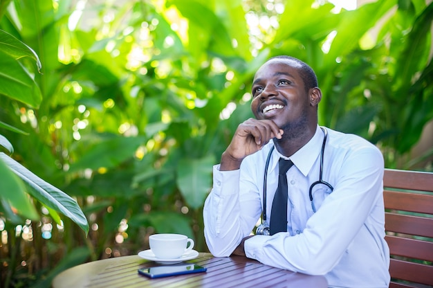 African doctor man is planning his future. he is sitting and smiling with the green nature background. Premium Photo