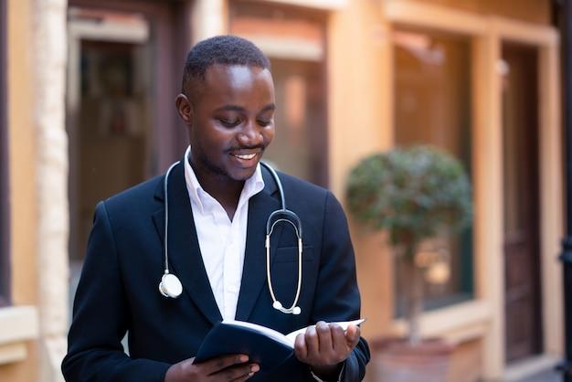 現代のクリニック病院の建物の近くの本を読んで古典的なスーツを着て聴診器でアフリカの医師 Premium写真