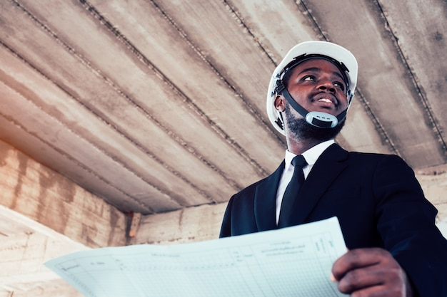 African engineer man architect looking at construction project Premium Photo