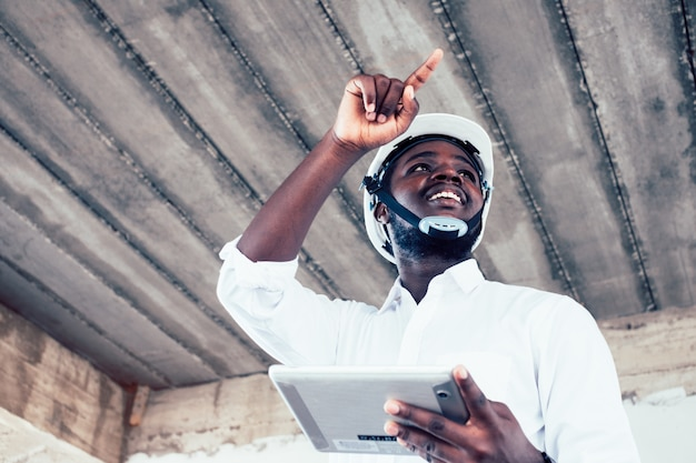 African engineer man architect looking and holding construction project on tablet Premium Photo