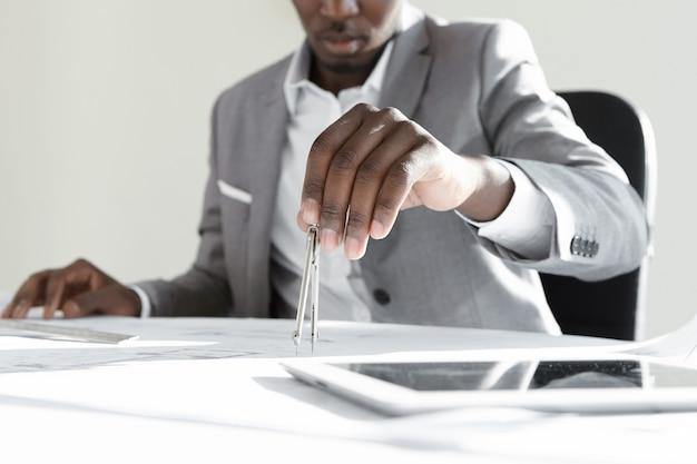 측정 계산에 기술 드로잉 도구를 사용하는 아프리카 엔지니어 무료 사진