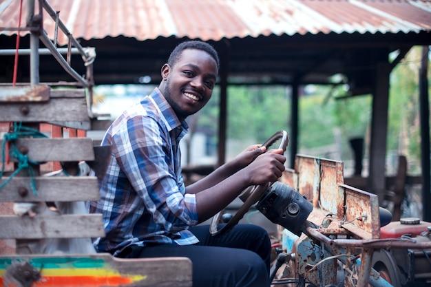アフリカの農夫の男が田舎で小さなトラクターを運転する Premium写真