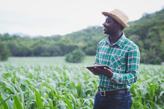 Африканский фермер стоит на зеленой ферме Premium Фотографии