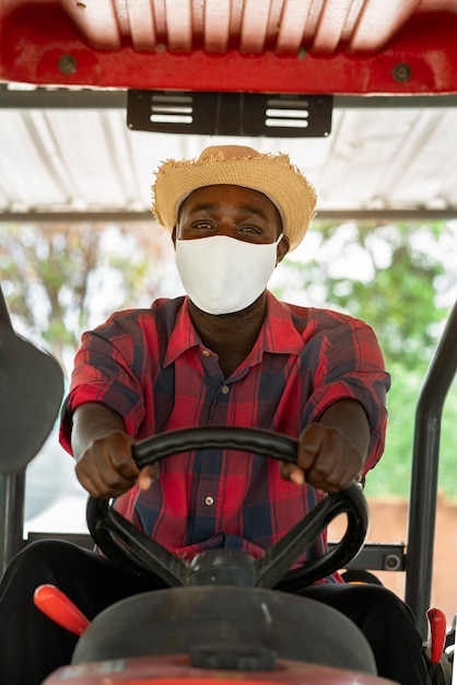 African farmer wear face mask and driving tractor in farm during harvest in countryside. agriculture or cultivation concept Premium Photo