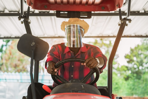 African farmer wear  face shield and driving tractor in farm during harvest in countryside. agriculture or cultivation concept Premium Photo