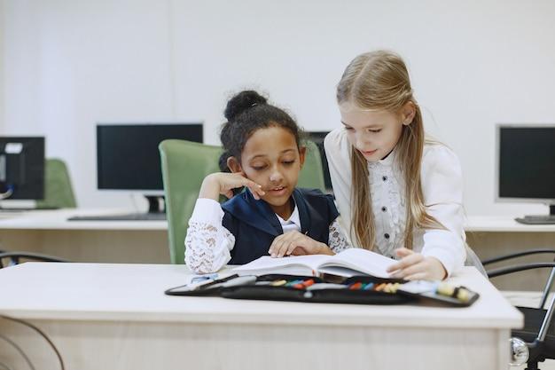 テーブルに座っているアフリカの女の子。女子学生は休憩中に本を読みます。子供たちはコンピュータサイエンスのクラスに座っています。 無料写真