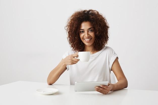 ホールディングカップと白い壁の上のテーブルに座っているタブレットを笑顔のアフリカの女の子。 無料写真