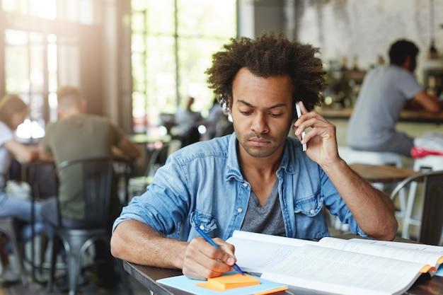 黒い肌と豊かな髪を持つアフリカの大学院生の男性が彼の卒業証書用紙で働いて、スマートフォンで彼の研究監督者に相談しているカフェの木製の机に座っている重要なアイデアを書き留めている 無料写真