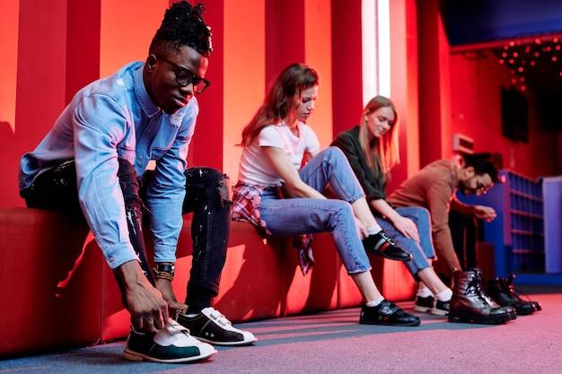黒のジーンズとデニムシャツを着たアフリカ人の男が壁に沿って赤い革のベンチに座って、試合前にボウリングの靴を履いています Premium写真