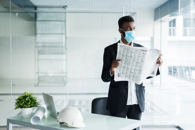 African handsome business man in medical mask reading the newspaper at office building Free Photo