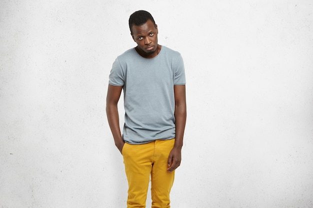 African male in casual t-shirt and mustard pants, looking at camera with guilty expression Free Photo