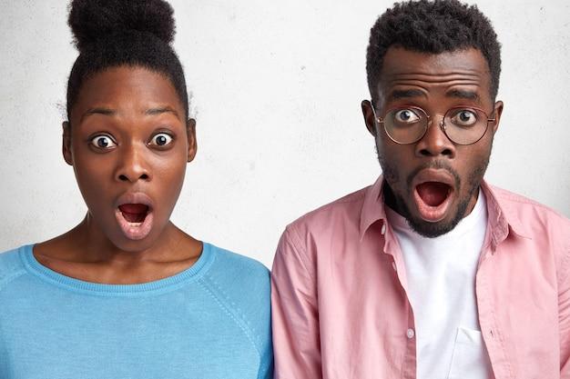 Studenti africani maschi e femmine guardano increduli con la bocca aperta, scoprono l'esame di domani, hanno espressioni scioccate Foto Gratuite