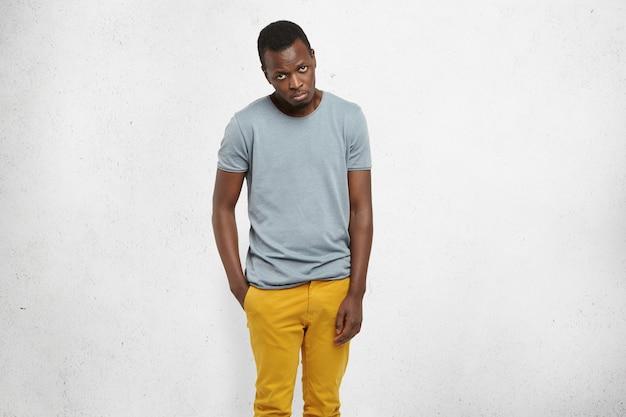 Африканский мужчина в повседневной футболке и горчичных штанах смотрит в камеру с виноватым выражением лица Бесплатные Фотографии