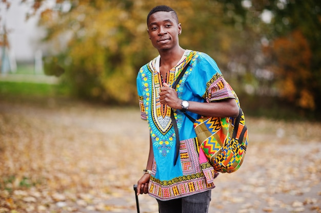 African man in africa traditional shirt on autumn park with backpack and suitcase. emigrant traveler. Premium Photo