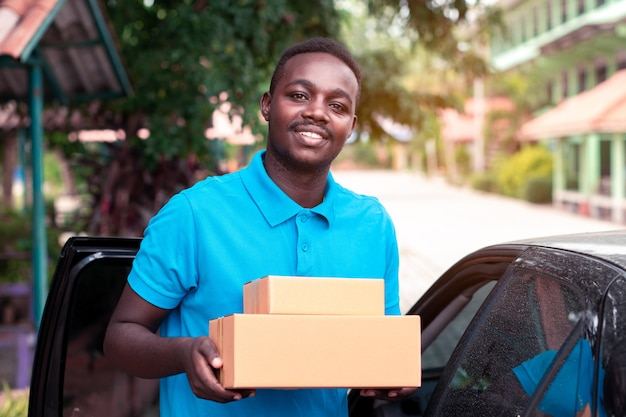 African man carrying package from delivery car Premium Photo
