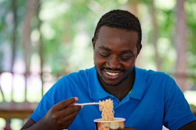 African man eating instant noodle soup for lunch Premium Photo