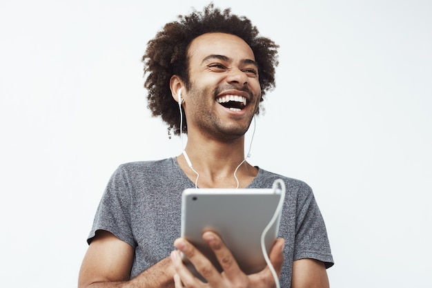 African man in headphones laughing holding tablet talking or watching and enjoying a comedy show or browsing. Free Photo