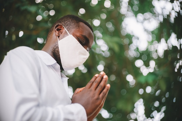 African man praying for god with wearing face mask Premium Photo