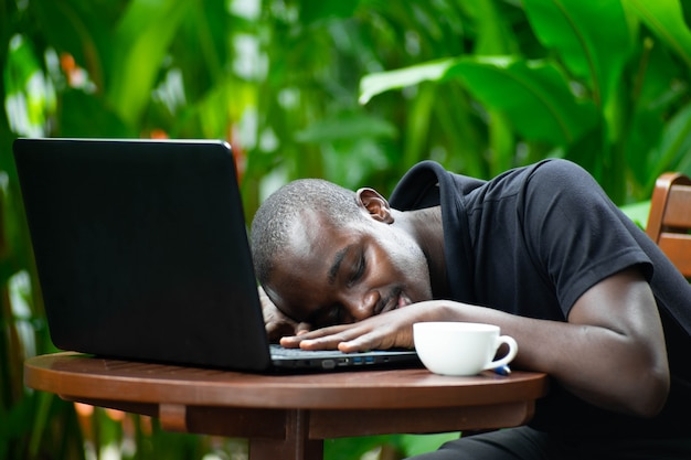 African man sleeping on laptop with green nature. Premium Photo