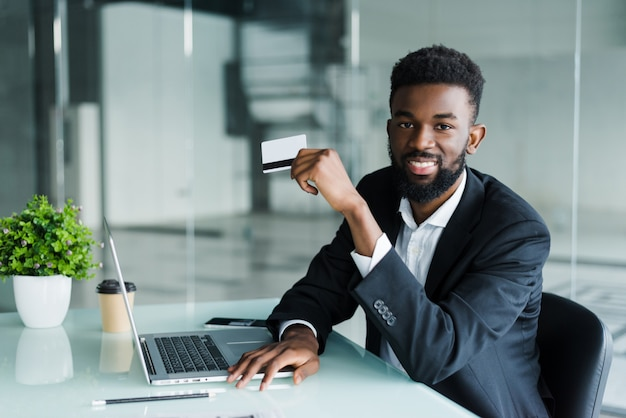African man talking on phone and reading credit card number while sitting at office Free Photo