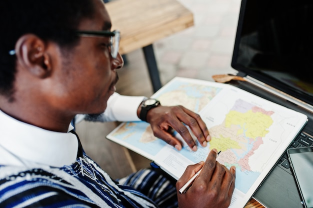 African man in traditional clothes and glasses sitting behind laptop at outdoor caffe and looking on map of africa and ghana at his notebook Premium Photo