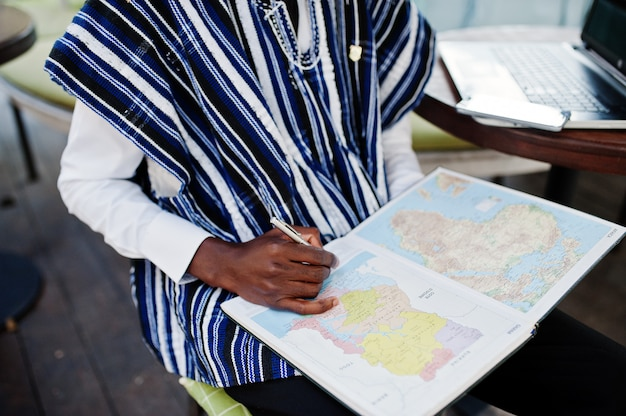 African man in traditional clothes sitting behind laptop at outdoor caffe and looking on map of africa and ghana at his notebook Premium Photo