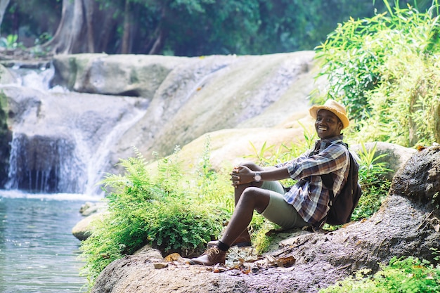 African man traveler  relaxing freedom at waterfall Premium Photo