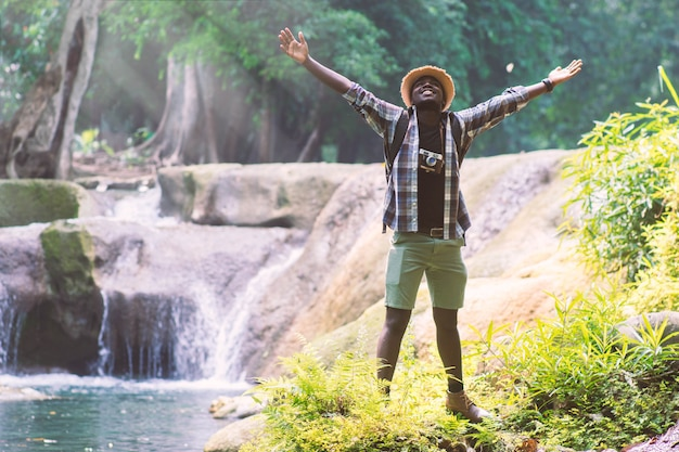 African man traveler with backpack standing and relaxing freedom at waterfall Premium Photo