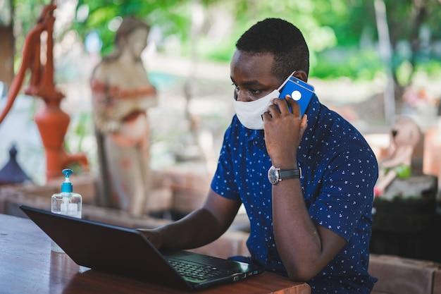 마스크를 쓰고 집에서 노트북을 사용하는 아프리카 남자. Whf 또는 Work From Home 개념 프리미엄 사진