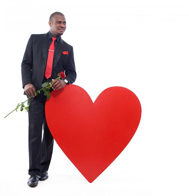 エレガントなスイートのポーズをとって、よそ見と笑顔で、赤いバラを手に持って、大きな赤いハートにもたれてアフリカ人。 無料写真