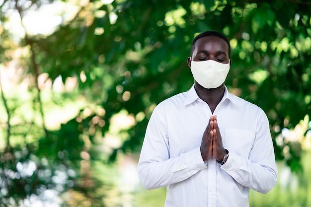 African man with face mask praying to fight coronavirus epidemic Premium Photo