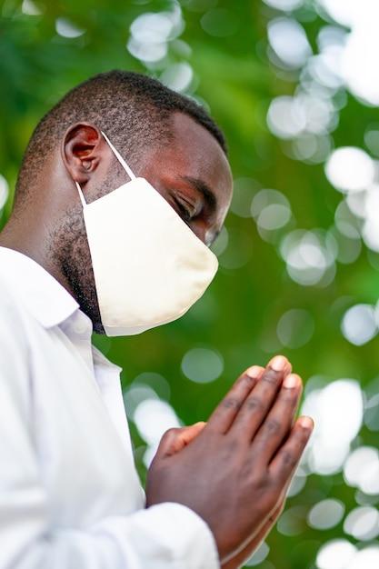 コロナウイルスの流行と戦うために祈っているフェイスマスクを持つアフリカ人 Premium写真