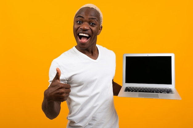 African man with white hair smiling holding laptop screen forward with mock up on yellow background Premium Photo