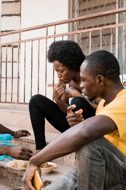 階段で食べるアフリカの人々 無料写真