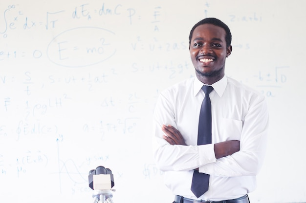 African science teacher teaching and smiling in the stem class with microscope. Premium Photo