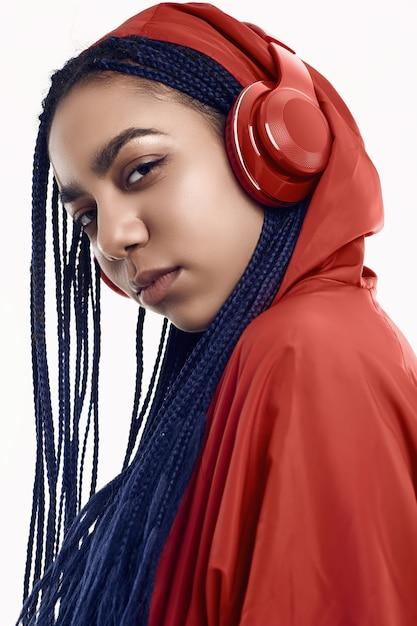 African teenage girl with dreadlocks in red windbreaker listening music Premium Photo
