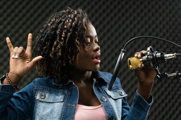 African teenager woman afro hair sing a song Premium Photo