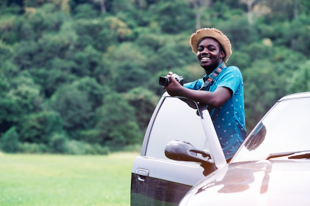African travelers  standing and holding camera with car Premium Photo
