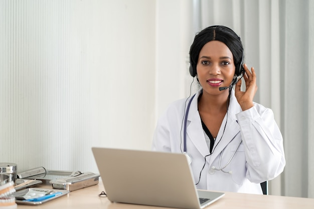 African woman doctor in headset taking calling on her headset microphone online for a ache patient Premium Photo