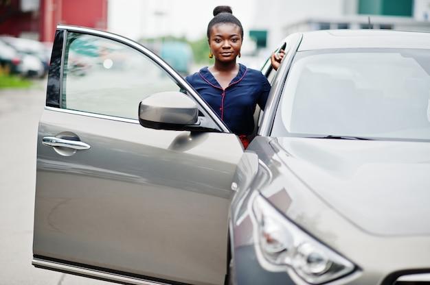 オレンジ色のズボンと青いシャツを着たアフリカの女性が開かれたドアと銀のsuv車に対して提起 Premium写真