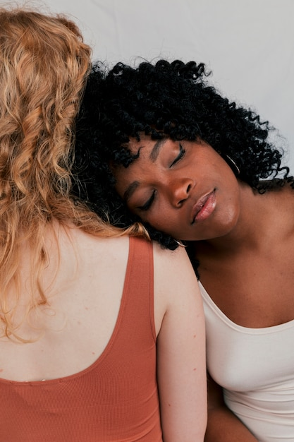 An african woman leaning on blonde fair woman's shoulder Free Photo