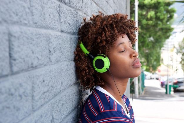 African woman listening to music with headphones Premium Photo