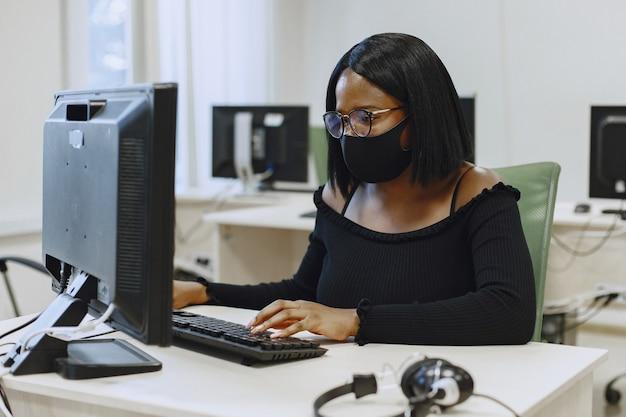 コンピュータサイエンスのクラスに座っているアフリカの女性。眼鏡をかけた女性。コンピューターの前に座っている女子学生。 無料写真